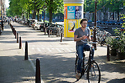 In Amsterdam rijdt een jongen al kijkend op zijn telefoon langs de gracht op de fiets.<br /> <br /> In Amsterdam a man is riding his bike while watching his phone.