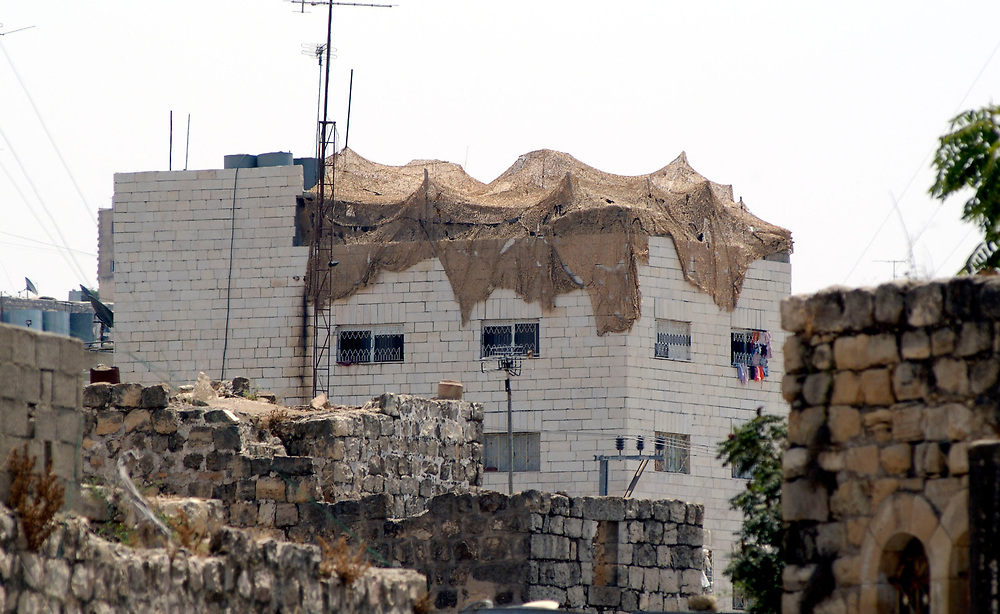 The Israeli military commonly takes over the rooftops of civilian homes to use as a sniper position in the middle of Palestinian towns, as here in Hebron.