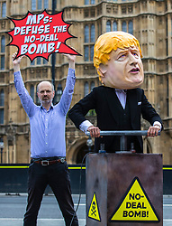 """© Licensed to London News Pictures. 03/09/2019. London, UK. Campaigners from Avaaz hold a photocall outside Parliament with a man dressed as Prime Minister Boris Johnson pushing the plunger on a """"No-Deal Bomb"""". MPs return from recess today and may vote on legislation to block a no deal exit from the European Union. Photo credit: Rob Pinney/LNP"""