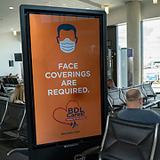 Signage from the Connecticut Department of Health alerts passengers who arrive at Bradley International Airport to wear face masks on Friday, July 31, 2020 in Windsor Locks, Connecticut. Per Governor Lamont's recent executive order,  passengers arriving from states with significant community spread of COVID-19 need to fill out a travel form and self-quarantine for 14 days or the length of their trip.  (Alex Menendez via AP)