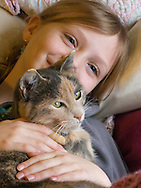 Young smiling blonde girl cuddling with the family cat
