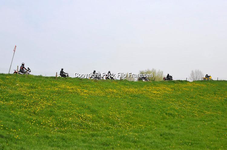 Nederland, Ooijpolder, 17-4-2020 Nu het wat warmer wordt en de zon uitbundig schijn halen motorbezitters hun tweewielers weer van stal en is het op de dijk langs de maas een drukte van belang van groepjes toerende motormuizen, fietsers en autos . Foto: ANP/ Hollandse Hoogte/ Flip Franssen
