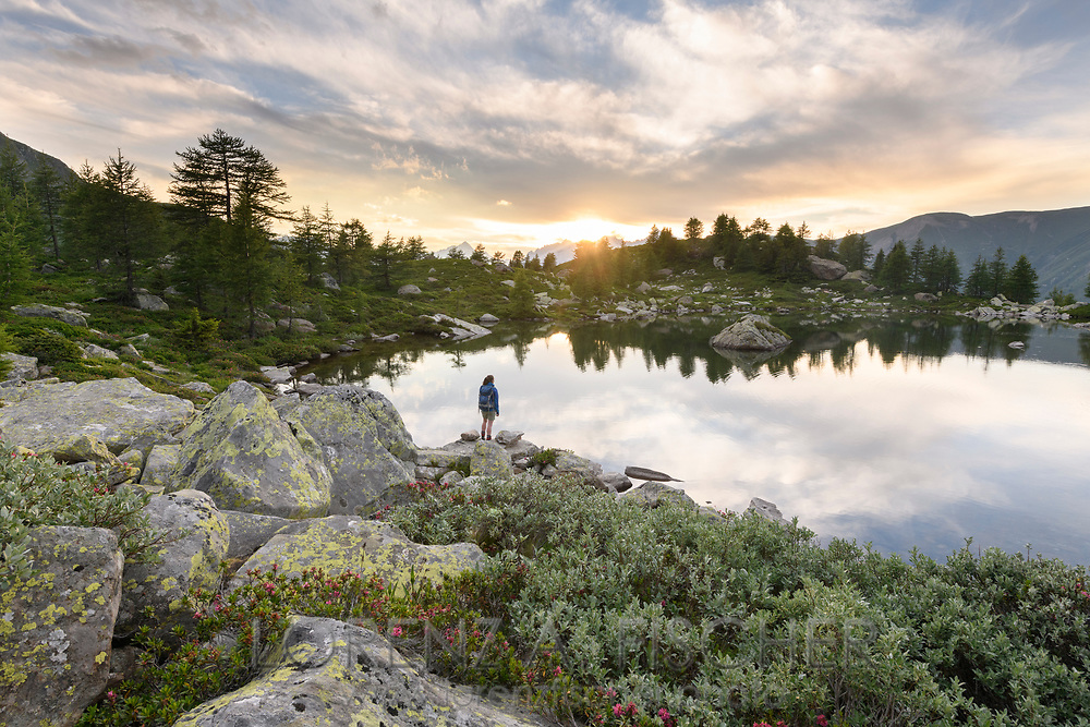 A female hiker is enjoying the sunset at the lake Mässersee , Landschaftspark Binntal, Valais, Switzerland