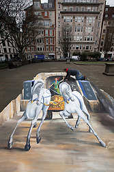© Licensed to London News Pictures. 30/01/2012. LONDON, UK. Artist Rick Cook uses chalk to finish off a 3D art piece in Golden Square, London, today (30/01/12). The drawing depicts a Boadicea type chariot drawn by horses emerging from a tunnel. Photo credit: Matt Cetti-Roberts/LNP