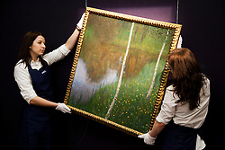 © Licensed to London News Pictures. 01/02/2012. LONDON, UK. Two Sotherby's gallery assistants adjust Gustav Klint's 1901 oil painting 'Seeufer mit Birken' (Lakeshore with Birches). The piece is estimated to fetch £6,000,000-8,000,000 at an auction taking place on the 8th of February 2012. Photo credit: Matt Cetti-Roberts/LNP
