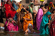 Indian Hindu pilgrims bathing and praying in The Ganges River at Dashashwamedh Ghat in Holy City of Varanasi, Benares, India