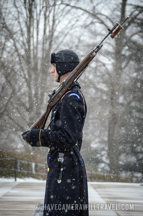 A soldier stands guard in the falling snow at the Tomb of the Unknowns at Arlington National Cemetery in the snow. The guard on duty engages in a set routine in which he marches 21 steps down the black mat behind the Tomb, turns, faces east for 21 seconds, turns and faces north for 21 seconds, then takes 21 steps down the mat and repeats the process.