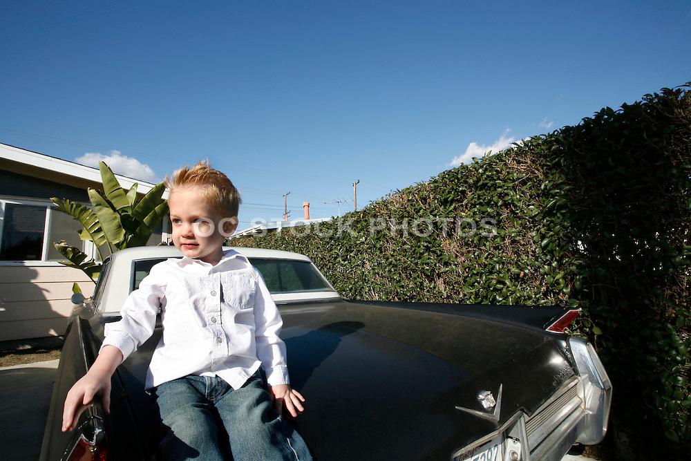 Young Boy Sitting On A Black Classic Cadillac