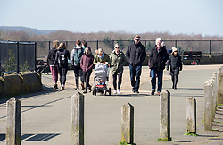 © Licensed to London News Pictures; 22/03/2020; Bristol, UK. Coronavirus Pandemic; people take a walk in the open air on Bristol's Downs on a sunny weekend, after the UK's prime minister ordered the closure of all pubs, bars, cafes, restaurants and indoor gyms to try and prevent the spread of the coronavirus. The UK Government is urging people to maintain social distance but also to get fresh air and exercise outside with social distance between people. Photo credit: Simon Chapman/LNP.