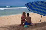 A father and his small daughter gaze out at the waves on the north shore of Oahu in Hawaii
