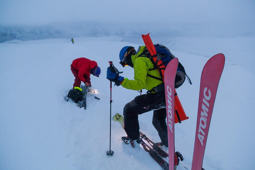 Nate Stevens (front) and Michelle Blade prepare to ski off the summit of Trollsteinen, Svalbard.