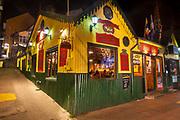 'Irish pub'  & pizzaria lit up at night, old cafe on main street, Ushuaia, Argentina.
