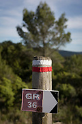 Detail of red and white stripes and signpost showing cross-country walkers the route on French national trekking network, the GR36, on 21st May 2017, in Lagrasse, Languedoc-Rousillon, south of France. Lagrasse is listed as one of France's most beautiful villages and lies on the famous Route 20 wine route in the Basses-Corbieres region dating to the 13th century.