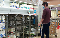 © Licensed to London News Pictures. 31/07/2021. London, UK. A shopper wearing a face covering walks looks at nearly-empty shelves of milk in Sainsbury's, north London. The UK's biggest milk processor, Arla Foods UK, has said that about 600 individual stores out of the 2,400 that it routinely supplies missed a delivery due to the pingdemic and a lack of lorry drivers. The pingdemic has seen staff shortages at supermarkets, resulting in less stock making its way to supermarket shelves. Photo credit: Dinendra Haria/LNP