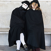 VENICE, ITALY - FEBRUARY 19:  A couple wearing a costume poses in St Mark Square ahead of the opening ceremony of the Carnival 2011 on February 19, 2011 in Venice, Italy. The fountain pouring wine features today during the Gran brindisi a Venezia or Grand Toast in Venice, the opening ceremony of this year Carnival .