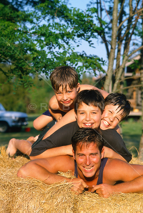 Three boys and a man piled on top of one another while outdoors on hay