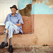 A portrait of an older Cuban man sitting on his doorstep in the town of Trinidad, Cuba.