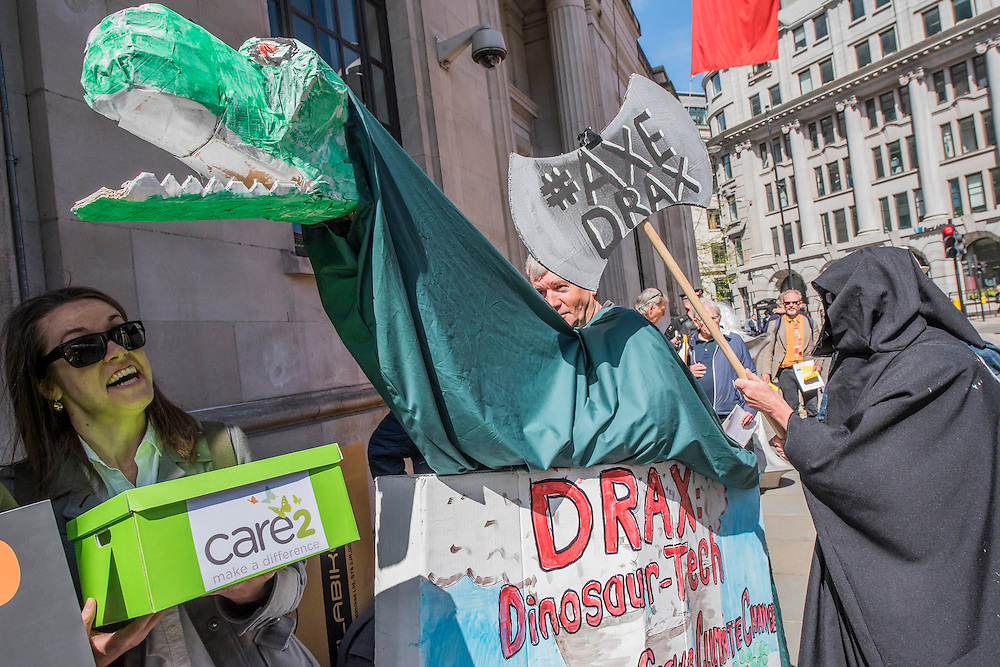 A puppet Draxosaurus symbolises their view that Drax should be extinct technology or at least shoul be axed (in this case by the grim reaper) - #AxeDrax protest outside the annual Drax shareholder AGM. Protestors demanded cleaner, greener energy generation systems. They continued on to the Department of Energy and Climate Change to deliver a petition demanding that subsidies given to Drax, for burning biomass, be stopped for making climate change worse.