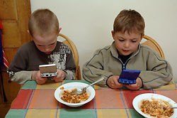 Two 5 year old friends playing their gameboys at kitchen table UK