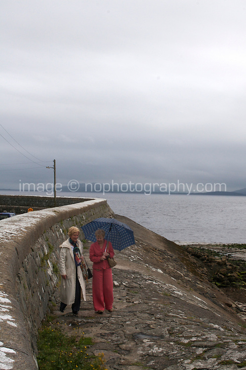 Two women walking in the rain at the back of a pier in Galway Ireland