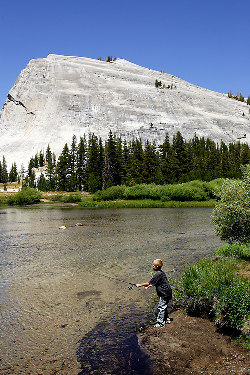 A young boy fishes Tuolumne River  with Lembert Dome looming above in Yosemite National Park