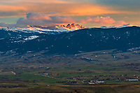 Blacktooth Mountain and Cloud Peak glow in the light of sunset on a windy evening. This view is from Soldier Ridge west of Sheridan and in the valley below is the small ranching community of Beckton.