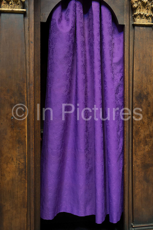 Purple Catholic confessional curtains in St Vitas Cathedral in Prague Castle, on 18th March, 2018, in Prague, the Czech Republic. The Metropolitan Cathedral of Saints Vitus, Wenceslaus and Adalbert is a Roman Catholic metropolitan cathedral in Prague, the seat of the Archbishop of Prague. Until 1997, the cathedral was dedicated only to Saint Vitus, and is still commonly named only as St. Vitus Cathedral. This cathedral is a prominent example of Gothic architecture and is the largest and most important church in the country. It is located within Hradcany-Prazsky Hrad Prague Castle in the Czech capital.