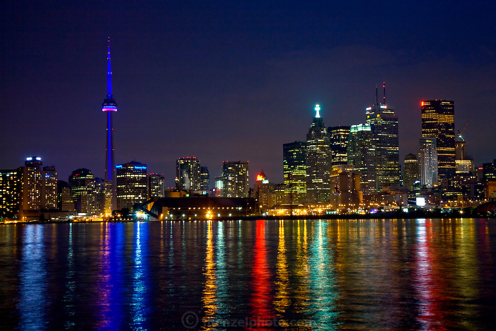 The CN Tower dominates the Toronto skyline in Ontario, Canada. (From the book What I Eat: Around the World in 80 Diets.) The 1,815-foot tower is illuminated by a recent multimillion-dollar lighting upgrade, and its nightly hues mirror the Canadian flag's colors of red and white. On Lake Ontario.