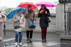 © Licensed to London News Pictures. 14/05/2015. London, UK. Women with umbrellas during heavy rain and wet and windy weather in Westminster, central London today. Photo credit : Vickie Flores/LNP