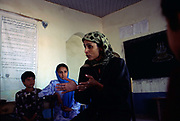 A teacher adresses schoolgirls in a classroom in Mazar-i-Sharif, Afghanistan. Traditionally, a girl's education was considered less important than boys - during the rule of the Taliban it was thought of as un-Islamic.