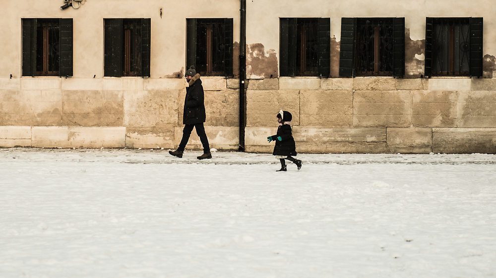"""VENICE, ITALY - 28th FEBRUARY/01st MARCH 2018<br /> A little girl runs in the snow during a snowfall in Venice, Italy. A blast of freezing weather called the """"Beast from the East"""" has gripped most of Europe in the middle of winter of 2018, and in Venice A snowfall has covered the city with white, making it fascinating and poetic for citizen and tourists.   © Simone Padovani / Awakening"""