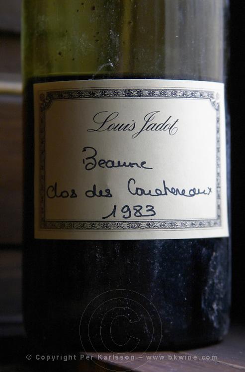 A half empty dusty old bottle with a hand written label saying Louis Jadot Beaune Clos des Couchereaux 1983 Burgundy red wine side-lit side light, closeup, Maison Louis Jadot, Beaune Côte Cote d Or Bourgogne Burgundy Burgundian France French Europe European