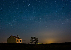 The evening sky reveals stars over the Lower Fox Creek Schoolhouse located in the Tallgrass Prairie National Preserve in the Kansas Flint Hills. The school, on the National Historic Register of Historic Places, was built on land donated by cattleman Stephen F. Jones. Built in 1882, the one-room school had its first classes in 1884. Typical enrollment was between one to 19 students of all grades. The school was closed in 1930 and restored in 1968 by the Garden Clubs in the Mid-East District of Kansas. The glowing light is from the city of Emporia some 20 miles away to the east. The 10,894-acre Tallgrass Prairie National Preserve is located in Chase County near the towns of Strong City and Cottonwood Falls. Less than four percent of the original 140 million acres of tallgrass prairie remains in North America. Most of the remaining tallgrass prairie is in the Flint Hills in Kansas.  Tallgrass Prairie National Preserve is the only unit of the National Park Service dedicated to the preservation of the tallgrass prairie ecosystem. The Tallgrass Prairie National Preserve is co-managed with The Nature Conservancy.
