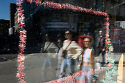 Passers-by and the  remnants of Christmas still occupies the window of a closed small business in the West End, during the third lockdown of the Coronavirus pandemic, on 29th March 2021, in London, England.
