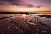 Sunset and clouds over streams and rivulets flowing down the huge sandy beach at low tide at Traeth Harlech, Tremadog Bay, North Wales