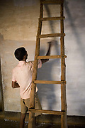 Indian man painting the walls of his house. Coorg or Kadagu is the largest coffee growing region of India, in the state of Karnataka, the inhabitants - the Kodavas have been cultivating crops such as coffee, black pepper and cardamon for many generations.