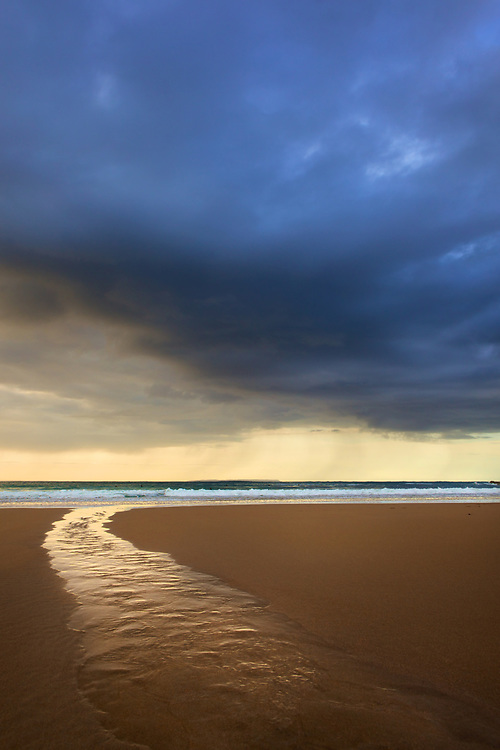 Water stream over the sand on a stormy day with dark clouds at Plemont beach, Jersey, Channel Islands