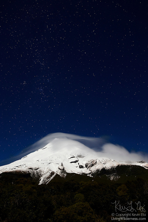 New Zealand's Taranaki, also known as Mount Egmont, capped by a lenticular cloud, glows by the light of the full moon under the night sky. The Southern Cross is visible near the top left.
