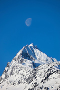 The moon hovers over Alpha Mountain, a 2305-meter (7562-feet) peak in Tantalus Provincial Park, British Columbia, Canada. The mountain is located near the town of Brackendale.