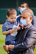 17 SEPTEMBER 2020 - DES MOINES, IOWA: INSANULLAN ANWARY, originally from Afghanistan, holds his son during a naturalization ceremony at Principal Park, a minor league baseball stadium in downtown Des Moines. About 75 people from 32 countries were naturalized as US citizens Thursday. It was the last citizenship ceremony in Des Moines before citizenship fees dramatically increase. Starting Oct. 2, the fee to apply for U.S. citizenship will increase from $640 to $1,160 if filed online, or $ 1,170 in paper filing, a more than 80% increase in cost. Advocates for immigration are afraid the new fees will be too expensive for many immigrants and say it's an effort by the Trump Administration to limit the number of new citizens welcomed into the United States. Because of the COVID-19 pandemic, there has been dramatic slow down in the number of naturalization ceremonies this year.        PHOTO BY JACK KURTZ
