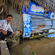 CAPTION: Mr Phuong in front of his family business, a small cafe on stilts which is becoming increasingly vulnerable as the water levels rise. He built a small concrete wall to prevent floodwater from further damaging the floor inside. LOCATION: An Binh Ward, Can Tho, Vietnam. INDIVIDUAL(S) PHOTOGRAPHED: Phan Van Phuong.