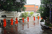 Buddhist monks walk in the rain at temple Wat Pho, Bangkok, Thailand.