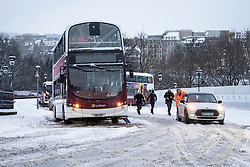 Edinburgh, Scotland, UK. 10 Feb 2021. Big freeze continues in the UK with heavy overnight and morning snow bringing traffic to a standstill on many roads in the city centre. Pic; People push car up The Mound to clear path for bus.  Iain Masterton/Alamy Live news