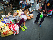30 AUGUST 2016 - BANGKOK, THAILAND: A woman rests in a Bangkok street after a food and clothing distribution at the Poh Teck Tung shrine on the last day of Hungry Ghost Month in Bangkok. Chinese temples and shrines in the Thai capital host food distribution events during Hungry Ghost Month, during the 7th lunar month, which is usually August in the Gregorian calendar.         PHOTO BY JACK KURTZ