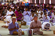 """12 JULY 2014 - PHRA PHUTTHABAT, SARABURI, THAILAND: People pray at the chanting service before the Tak Bat Dok Mai at Wat Phra Phutthabat in Saraburi province of Thailand. Wat Phra Phutthabat is famous for the way it marks the beginning of Vassa, the three-month annual retreat observed by Theravada monks and nuns. The temple is highly revered in Thailand because it houses a footstep of the Buddha. On the first day of Vassa (or Buddhist Lent) people come to the temple to """"make merit"""" and present the monks there with dancing lady ginger flowers, which only bloom in the weeks leading up Vassa. They also present monks with candles and wash their feet. During Vassa, monks and nuns remain inside monasteries and temple grounds, devoting their time to intensive meditation and study. Laypeople support the monks by bringing food, candles and other offerings to temples. Laypeople also often observe Vassa by giving up something, such as smoking or eating meat. For this reason, westerners sometimes call Vassa """"Buddhist Lent.""""<br />     PHOTO BY JACK KURTZ"""