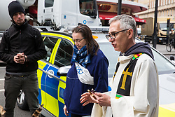 London, UK. 16th April 2019. A priest officiates at a religious service in Edgware Road during the second day of International Rebellion UK activities by climate campaigners from Extinction Rebellion to call on the Government to take urgent action to address climate change.