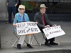 © Licensed to London News Pictures. 23/06/2018. London, UK. A couple sit and wait for the start of The People's Vote March for a second EU referendum near Trafalgar Square. Photo credit: Peter Macdiarmid/LNP
