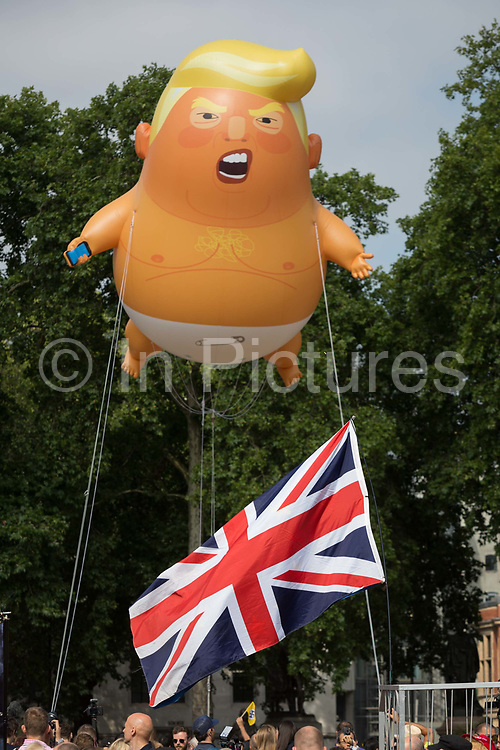 The inflatable balloon called Baby Trump flies above Parliament Square in Westminster, the seat of the UK Parliament, during the US Presidents visit to the UK, on 13th July 2018, in London, England. Baby Trump is a 20ft high orange blimp depicting the US President as an enraged, smartphone-clutching infant - and given special permission to appear above the capital by London Mayor Sadiq Khan because of its protest rather than artistic nature. It is the brainchild of Graphic designer Matt Bonner.