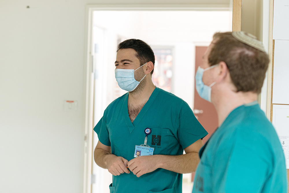 Dr. Fadi Kharouf (C) and Dr. Matan Fischer (R) laugh during their shift, outside an isolated ward for Covid-19 Novel Coronavirus patients, at the Hadassah Ein Kerem Hospital, in Jerusalem, Israel, on April 20, 2020.