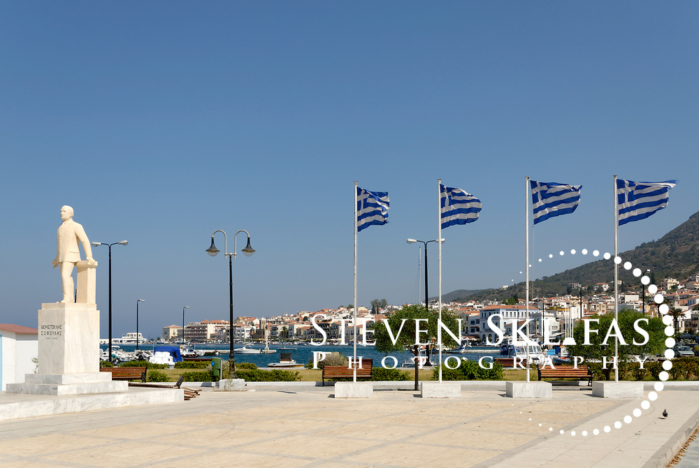 Samos. Greece. Themistoklis Sophoulis monument with four flags of Greece on the waterfront of Vathy or Samos town. Vathy is situated on a horseshoe shaped bay and is the capital and largest town of Samos.